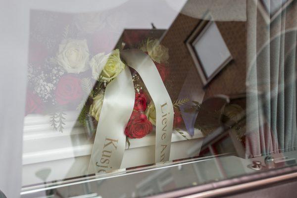 Een kist met linten en bloemen gezien door het raam van een rouwauto, afscheidsfotografie