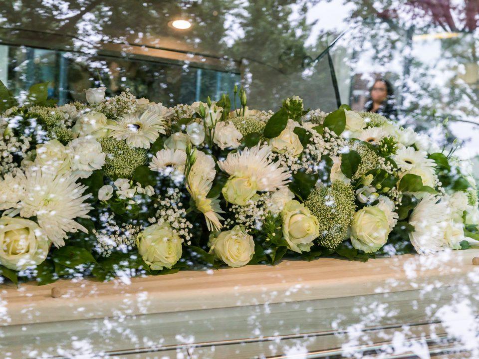 Bloemen in rouwauto, afscheidsfotografie