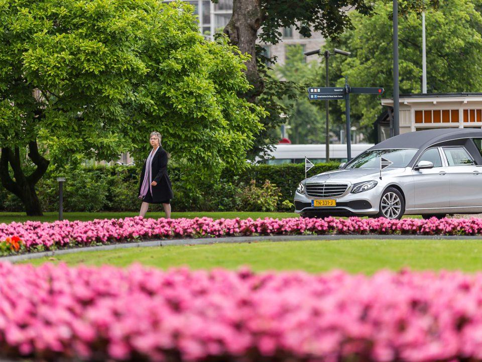 Uitvaartleidster loopt voor de grijze rouwauto, De Nieuwe Ooster, afscheidsfotografie