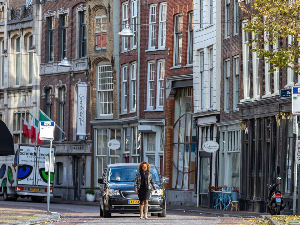 Uitvaartleidster loopt voor de rouwauto, afscheidsfotografie, Dordrecht binnenstad